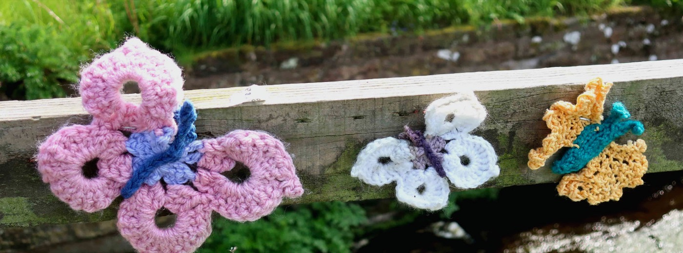 Knitted butterflies on a fence