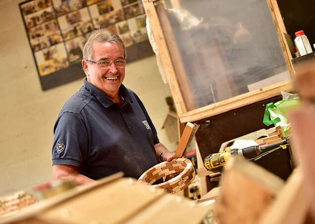 Man working hard in wood workshop smiling