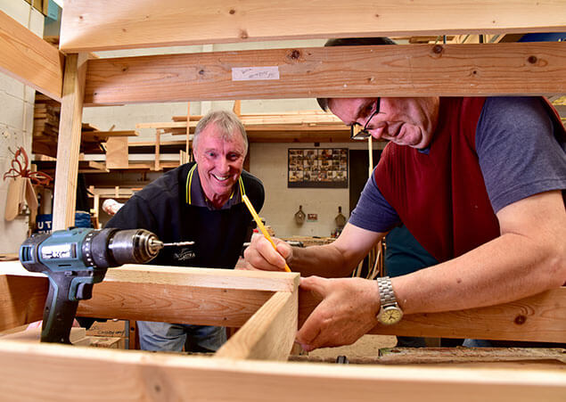Two men working hard in wood workshop smiling